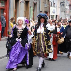 Turniej rycerski - Ludzie w starych strojach idą przez miasto