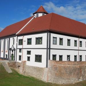 Zamek z białą elewacja i czerwonym dachem