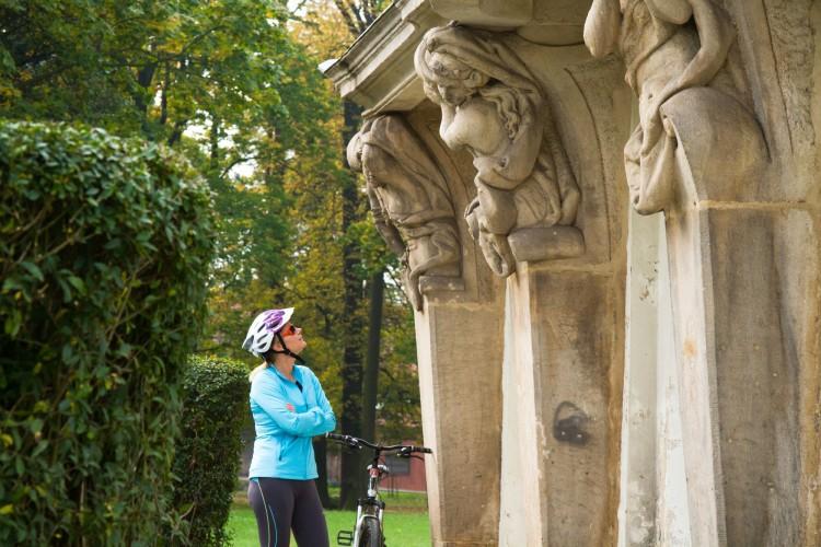 Kobieta w sportowym stroju ptrząca się na rzeźby