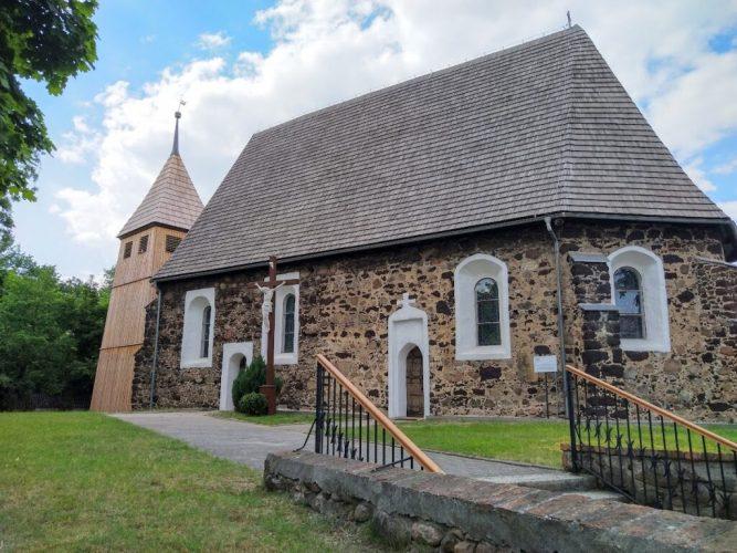 Niewielki budynek z kamienia ze spiczastym dwuspadowym dachem. Obok wieża kościelna. Wokłó zadbane trawniki. Słoneczna pogoda.