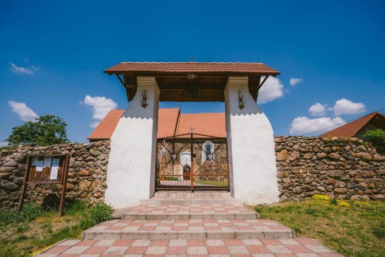 Mur z kamienia, a po środku brama prowadząca do kościoła.