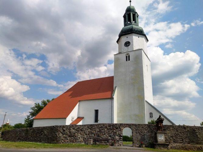 Biały budynek z wieżą kościelną, pomarańczowym dachem. Wokół mur z kamienia i figura.