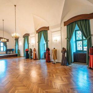 Duża sala z żyrandolami. Pod ściana 9 manekinów ubranych w stroje. Na podłodze parkiet z deseczek. Duże okna z ciężkimi, zielonymi zasłonami.