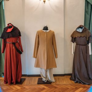 Trzy manekiny odziane w stroje średniowieczne.