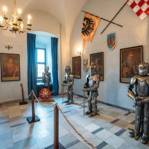 Pomieszczenie w Zamku. pod ścianą 4 metalowe zbroje rycerskie. za nimi wiszą obrazy przodków. chorągwie i herby. Przed zbrojami słupki z liną odgradzające ewentualnych zwiedzających.