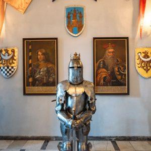 Jedna z sal w zamku. Na pierwszym planie trzy zbroje rycerskie. za nimi na ścianie wiszą obrazy przodków.
