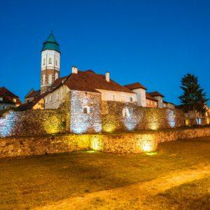 Po lewej stronie zdjęcia pięknie podświetlone mury miejskie z kamienia, w tle zabudowania.