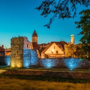 Mury miejskie i widok na stare miasto w Kożuchowie. Po lewej stronie zdjęcia pięknie podświetlone mury miejskie z kamienia, w tle zabudowania.