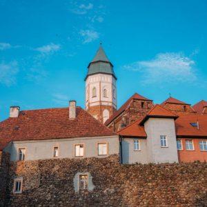 Na pierwszym planie fragment murów z kamienia, na drugim planie fragmenty zabudowań i wieża kościelna