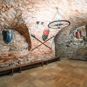 Niskie pomieszczenie. Ściany z cegieł. Na ścianach herby, pod ścianami niskie ławeczki.