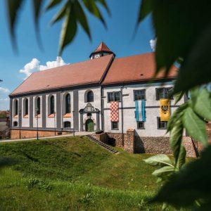 Widok na zamek w Kożuchowie. Prostokątna budowla ze spadzistym dachem. Z trzech okien wiszą flagi. chorągwie. Do zamku prowadzi ścieżka.