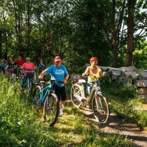 Grupa rowerzystów na trasie wśród zieleni. na pierwszym planie dwie panie prowadzą rowery. za nimi pozostali uczestnicy wycieczki rowerowej.