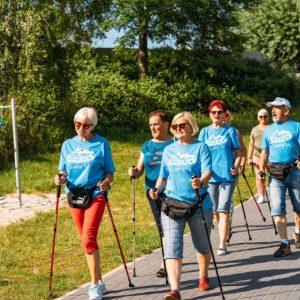 Grupa starszych osób z kijkami. Ubrani w jednakowe błękitne koszulki. Idą betonową ścieżką wśród zieleni.