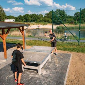Na pierwszym planie dwaj chłopcy grają w ping-ponga. Po lewej stronie zadaszona wiata. W tle kąpielisko, dalej drzewa.