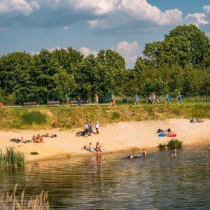 Kąpielisko. Na brzegu kilkanaście osób, część pływa w wodzie. Na drugim planie widoczna grupa osób z kijkami.