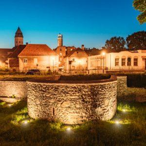 Mury miejskie i widok na stare miasto w Kożuchowie. Zdjęcie zrobione wieczorem, ładnie oświetlone mury i zbudowania. Błękitne niebo. Brak ludzi.