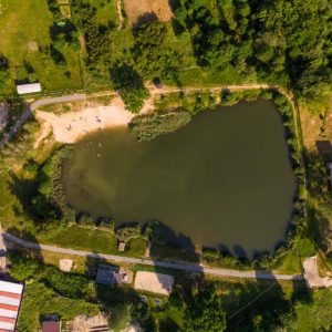 Zdjęcie z lotu ptaka - jezioro otoczone zielenią i zabudowaniami.